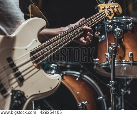 Close-up Of A Bass Guitar In The Hands Of A Musician In The Process Of Playing.