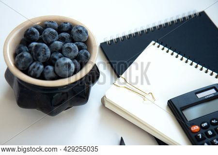 Calculator, Black And White Notepads And Blueberries In A Ceramic Bowl Isolated On White Background.