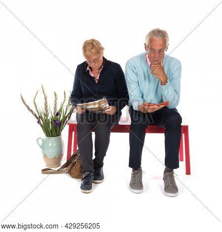 Senior couple sitting in waiting room isolated over white background