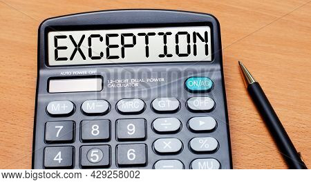 On A Wooden Table There Is A Black Pen And A Calculator With The Text Exception. Business Concept