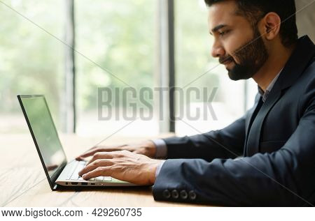 Serious Confident Young Indian Man Entrepreneur In Formal Suit Working On A Laptop Sitting At The De