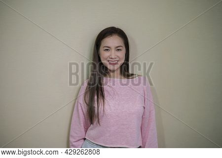 Smiling Black-haired Woman 40-year-old Woman Wearing A Casual Pink Sweater. Copy Space Isolated On P