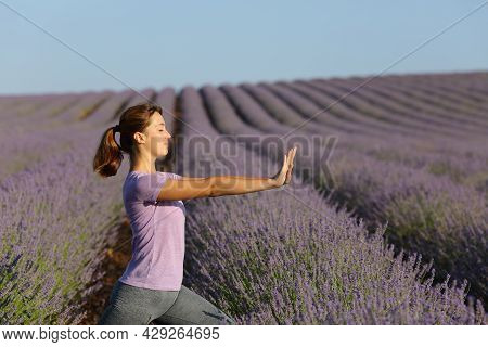 Profile Of A Woman Practicing Tai Chi Exercises In Lavender Field