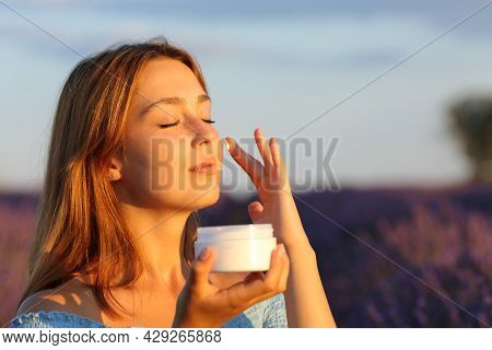 Beauty Woman Applying Moisturizer Cream On Cheek In Lavender Field At Sunset