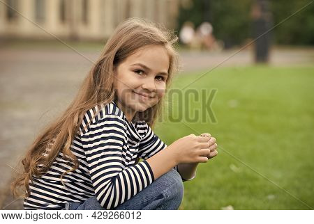 Lets Your Child Have Cared Better. Happy Child Sit On Haunches Outdoors. Little Girl Child In Casual