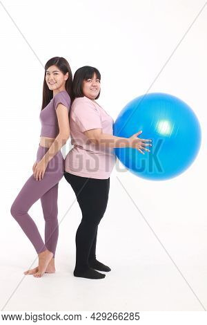 A Skinny Asian Woman And A Fat Woman Stand Next To Each Other. Put On Exercise Clothes, Play Yoga Ba