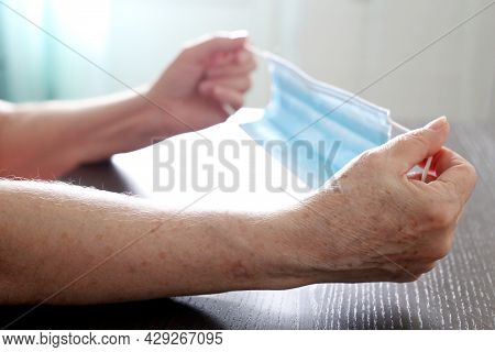 Elderly Woman With Medical Face Mask In Wrinkled Hands. Protection For Old People During Coronavirus
