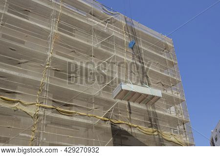 Crane With Load Of Drywall Panels Over Construction Site.  Working Under A Suspended Load Concept