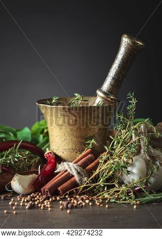 Herbs And Spices On A Wooden Table. Old Copper Mortar With Spices .