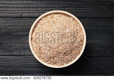 Bowl Of Wheat Bran On Black Wooden Table, Top View