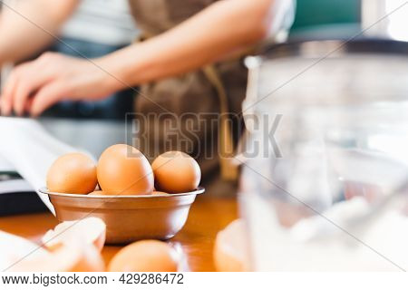 Selective Focus Of Chicken Eggs With Woman Baking Cake In Background