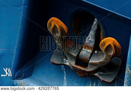 A Rusty Textured Anchor Of A Sea Vessel. The Blue Color Of The Ship, And Bright Orange Rust On The A