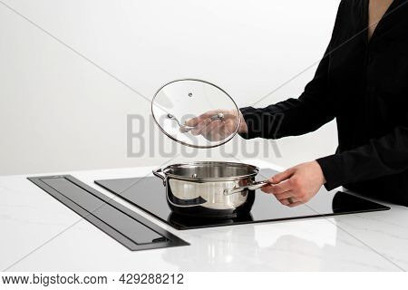 Cropped Shot Of Housewife In Dark Shirt Checking Inside Of Metal Pot On Induction Cooktop Integrated