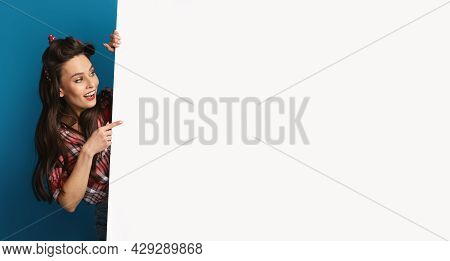 Cheerful Pinup Woman Peeking From Behind Blank White Poster, Showing Mockup For Logo, Design Or Adve