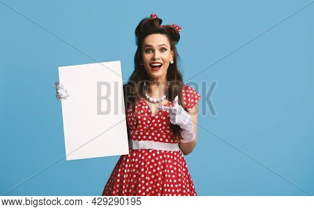 Cheerful Pinup Lady In Retro Outfit Holding Blank Advertising Board With Copy Space On Blue Backgrou
