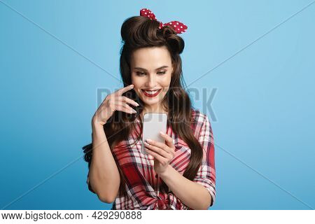 Flirty Pinup Woman In Retro Style Outfit Looking At Smartphone Screen, Browsing Internet, Checking S