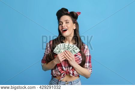 Overjoyed Young Pinup Woman Holding Big Sum Of Money Close To Heart, Excited Over Winning Lottery On