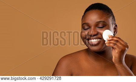 Portrait Of Chubby Black Woman Cleaning Skin By Cotton Pad