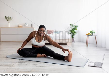 Plump Black Lady Stretching Legs, Practicing Yoga On Mat, Following Tutorial On Laptop, Doing Exerci