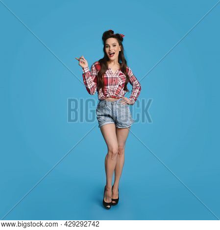 Full Length Of Sexy Young Pinup Woman In Retro Outfit Pointing Aside On Blue Background, Copy Space