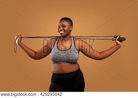 Young Black Chubby Woman Posing With Jumping Rope At Studio