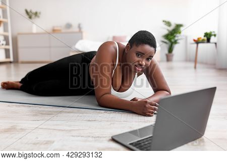 Exhausted Plump Black Woman Lying On Yoga Mat Near Laptop, Having No Strength For Home Training