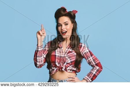 Young Pinup Lady In Retro Clothes Pointing Upwards On Blue Studio Background