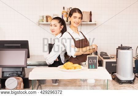 Wide Shot Of Beautiful Caucasian And Asian Barista Women Stand With Crossed Arms To Welcome Customer