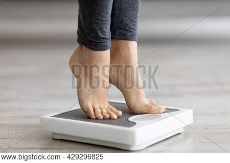 Closeup Of Young Indian Woman Standing On Scales, Measuring Her Weight Indoors