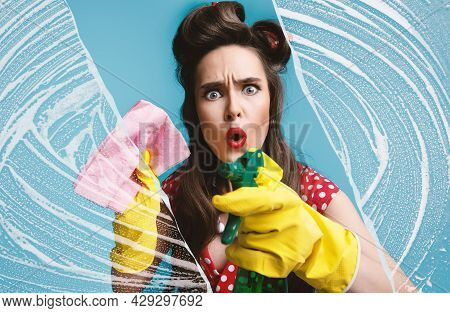 Terrified Pinup Woman In Retro Dress Cleaning Glass With Detergent And Rag, Wiping Soap Suds On Blue