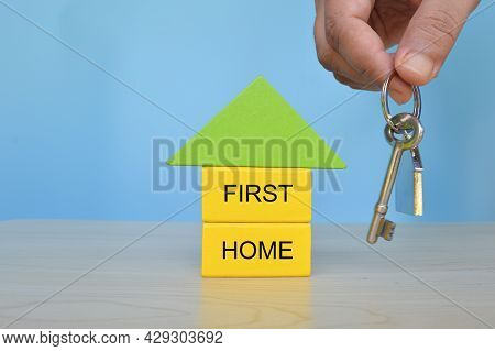 Hand Holding Key Beside The Home Model With Text First Home