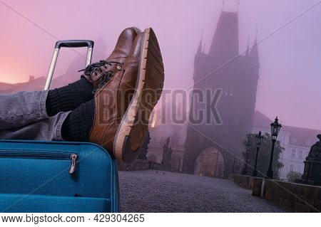 Tourist Is Relaxing At Charles Bridge In Prague With Legs On His Luggage. Travel Concept.