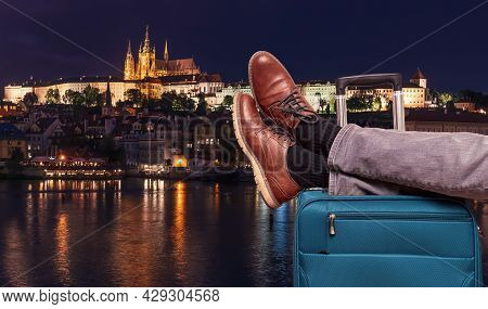 Tourist Is Relaxing Near Prague Castle At Night In Prague With Legs On His Luggage. Travel Concept.