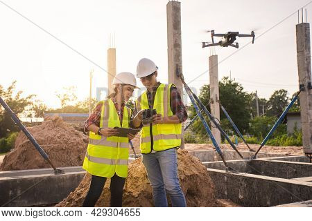 Team Engineer Surveyor Discussion In Project Construction Site Work. Teamwork Civil Engineer Use Dro