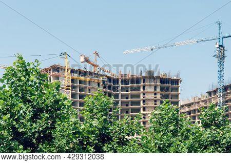 Construction Site Cranes. Crane And Building Construction Site Against Blue Sky.