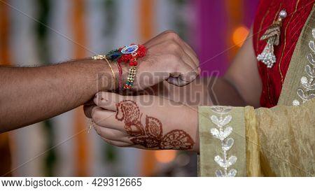Sister Tying The Rakhi, Raksha Bandhan To Brothers Wrist During Festival Or Ceremony - Raksha Bandha