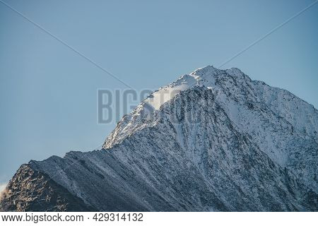 Minimalist Sunny Mountain Landscape With Snow-covered Mountain Top In Golden Sunshine In Clear Blue