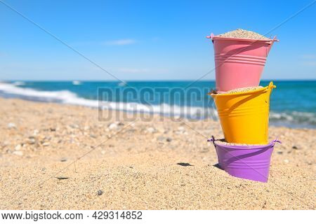 Colorful toy buckets at the beach