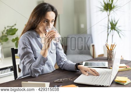 Young Business Woman Working At Home And Drink Glass Of Water. She Drinking Water While Working At T