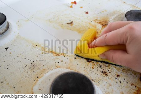A Hand With A Yellow Wash Sponge Washes The Very Dirty Greasy Surface Of The Gas Stove. After The Sp
