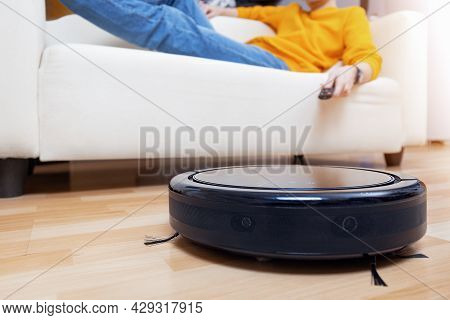 Man Resting On The Sofa, While The Robot Vacuum Cleaner Cleaning Living Room And Dust. Concept Time