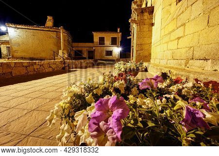 Romanesque Church At Night With Flowerpots Full Of Flowers.