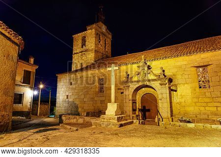 Romanesque Church At Night With Bell Tower And Stone Cross.