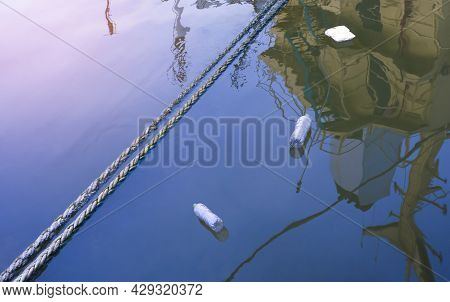Discarded Plastic Rubbish Bottles With Foam Box Floating On River Surface At Harbor In Evening Time