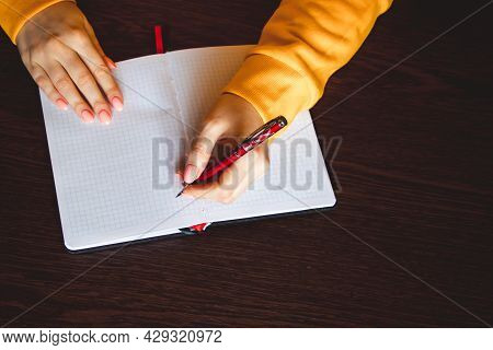 Woman Writes In A Notebook And Holds Pen With Her Left Hand. The Girl Works In The Office. Left-hand