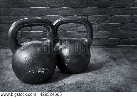 Two Black Rough And Scratched Kettlebells On A Dark Background.