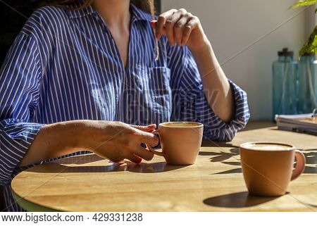 Women Hand And Coffee Cup On Wood Desk In Coffee Shop Or Cafe, Close Up.