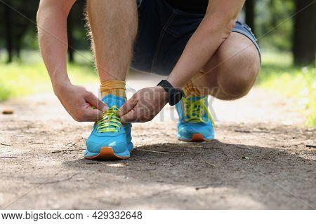 Runner Tying Running Shoes Closeup. City Man Shoelace Sneakers