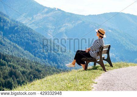 Young Fashionable Dressed Female In Straw Hat Sitting On A Bench Enjoying Santa Maddalena Village Vi