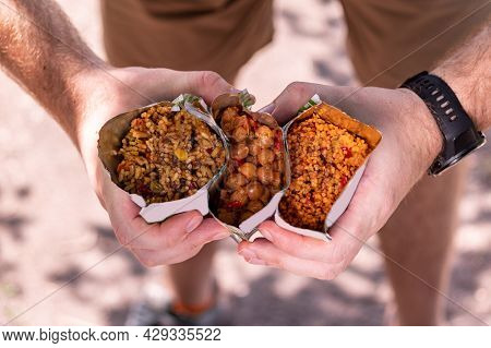 Diverse Tourist Food. Tourist Porridge In A Retort Package. Chickpea Porridge. The Tourist Is Holdin